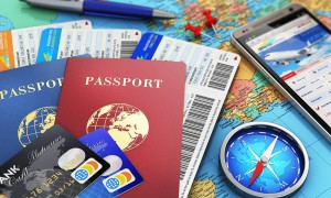 Creative abstract business travel and tourism concept: air tickets or boarding pass, passports, touchscreen smartphone with online airline tickets booking or reservation internet application, magnetic compass, credit cards and pen on world geographic map atlas with selective focus effect